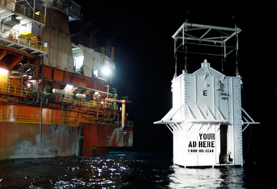 Giant container lowered into oil-fouled gulf